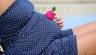 une rose posée sur le ventre d'une future maman