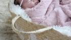 petite fille enveloppée dans un panier en osier