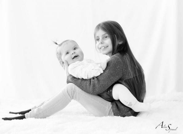 fillette tient sa petite soeur sur ses genoux