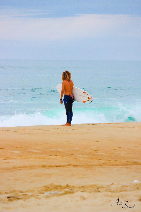 un surfeur regarde l'ocean