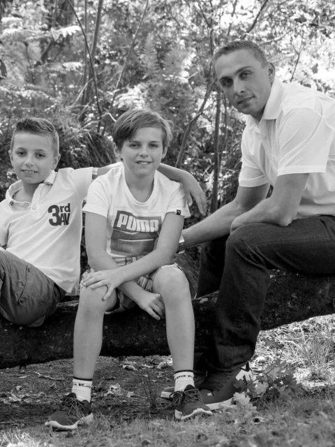 pere et ses fils sur un tronc d'arbre
