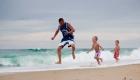 un père et ses fils sautent dans les vague