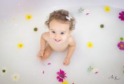 Un bain de lait pour les un an d'une petite fille