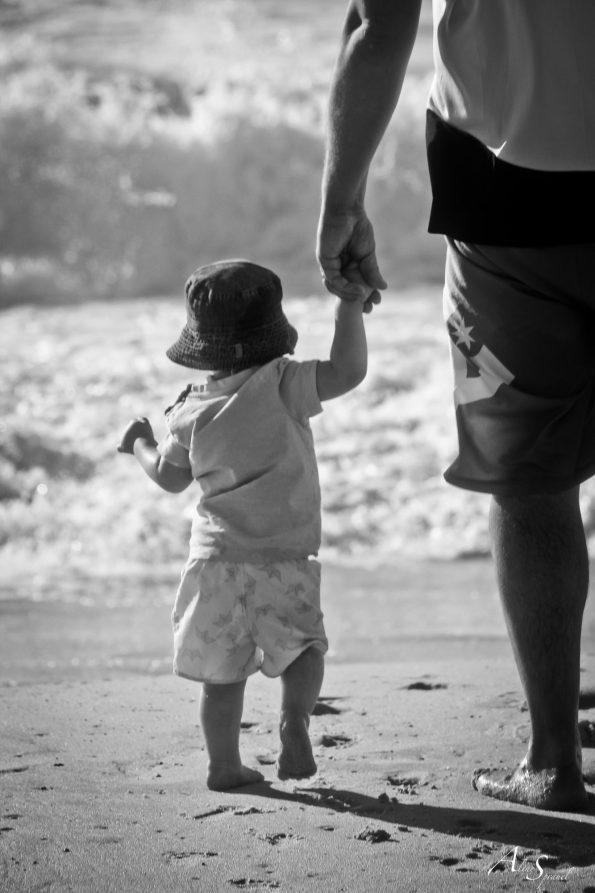 père tient la main de son fils