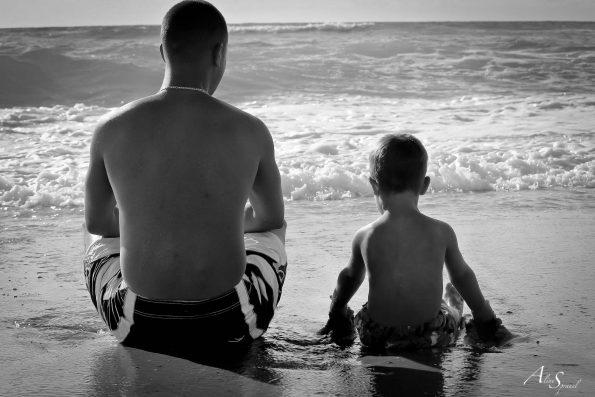 pere et fils assis a la plage